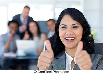 Portrait of a businesswoman with thumbs up in office