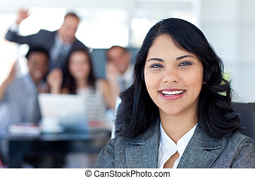 Portrait of a businesswoman smiling with her team celebrating a success in the background