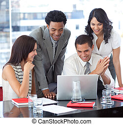 Multi-ethnic business team working together with a laptop in...