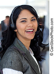 Smiling businesswoman with a headset on in company