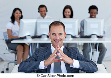 Smiling manager in call center in front of his team