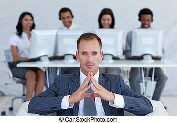 Serious manager in call center in front of his team