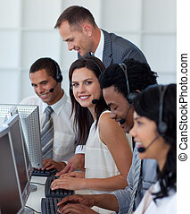 Businesswoman in a call center with her team and manager -...