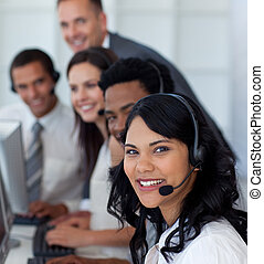 Portrait of a businesswoman in a call center with her team -...