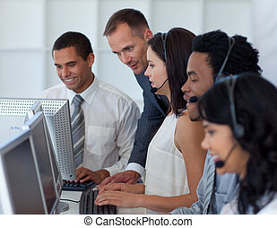 Young manager talking to his business team in a call center...