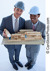 Engineers with hard hats holding a model house - High angle...