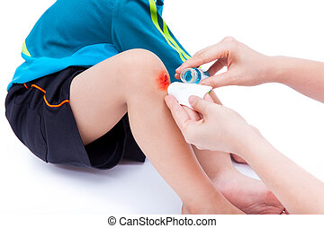 Mother clean and provides first-aid at wound on son leg,...
