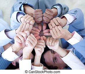 Close-up of business team on floor in a circle with thumbs...