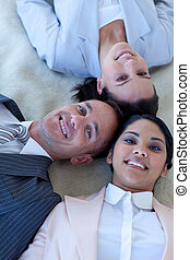Business team on floor with heads together smiling -...