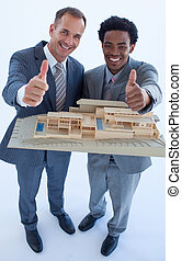 Architects holding a model house with thumbs up - High view...