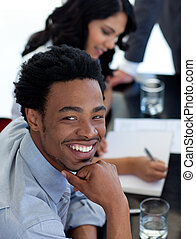 Portrait of a smiling Afro-American businessman in a meeting...