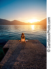 Woman sitting on the pier at sunrise - Lonely woman dreaming...