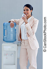 Businesswoman drinking from a water cooler in office