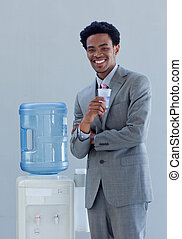 Businessman drinking from a water cooler in office -...