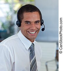 Smiling hispanic businessman working in a call center