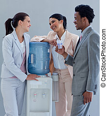 Business people speaking next to a water cooler in office