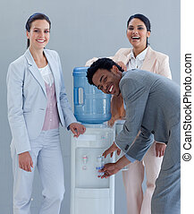 Business team drinking from a water cooler in office