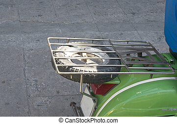 Black spare wheel under grill on green scooter motorcycle -...