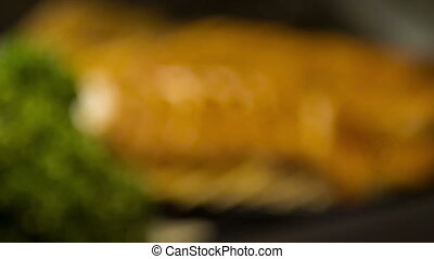 Selective focus on tasty conger eel lying on black plate -...