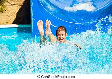 Man at water park - Man having fun, sliding at water park.
