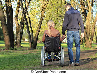 Couple wheelcair holding hands in park