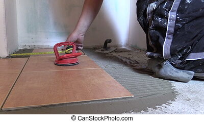 man measure tile floor - man measure with centimeter left...