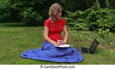 pregnant woman notebook - Beautiful pregnant woman look at...