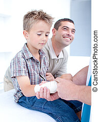 Young doctor bandagins a patient\'s arm in hospital