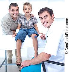 Doctor checking a boy reflexes - Doctor checking a little...