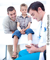Doctor bandaging a child\'s foot in hospital