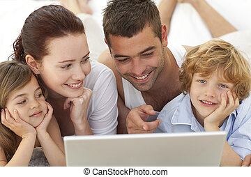 Portrait of family in bed using a laptop