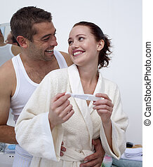Happy couple in bathroom holding a pregnancy test - Happy...