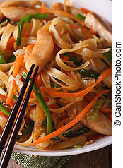 fried noodles with chicken and vegetables macro. vertical -...
