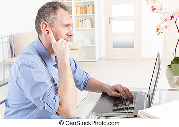 Hearing impaired man working with laptop at home or office