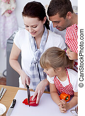 Smiling family cutting peppers in kitchen