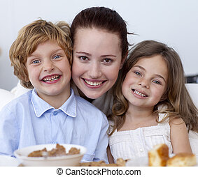 Portrait of children having breakfast with their mother