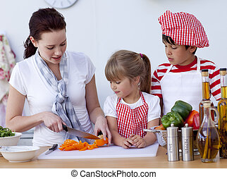 Children helping mother cooking in the kitchen - Smiling...