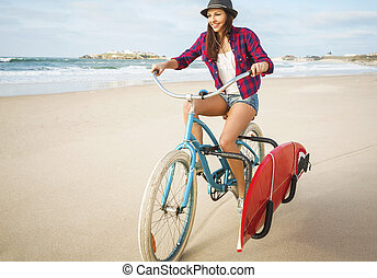 Going to Surf - Surfer young woman riding her bicycle on the...