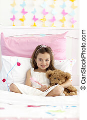 Smiling little girl writing in bed