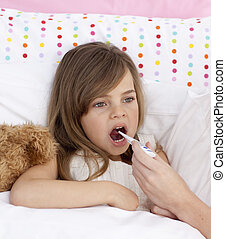 Mother taking her daughter\'s temperature in bed