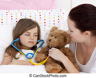Sick daughter playing with a stethoscope with her mother