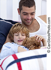 Portrait of father and son reading a book in bed