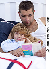 Little son reading with his father in bed
