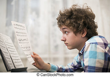 boy plays piano - A shot of teenager boy playing piano