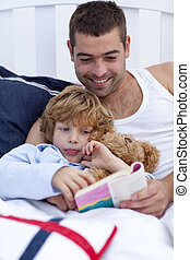 Little boy reading with his father a book