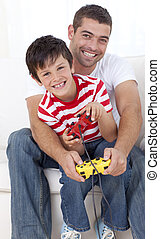 Father and son playing video games at home - Happy father...