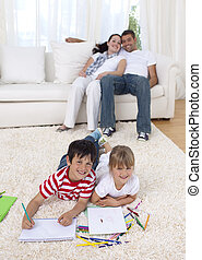 Brother and sister painting on floor in living-room with...