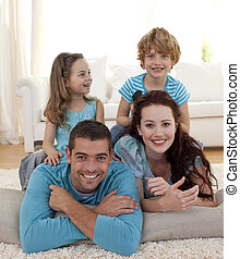 Parents, daughter and son on floor in living-room - Parents,...