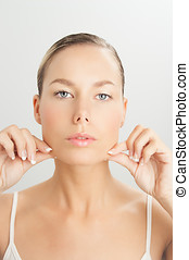 Face Massage - Elegant Caucasian woman doing face massage...