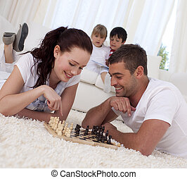 Smiling couple playing chess on floor in living-room with...
